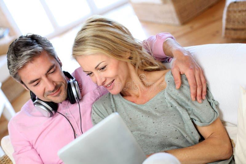Couples mûrs écoutant la musique avec le comprimé photos stock
