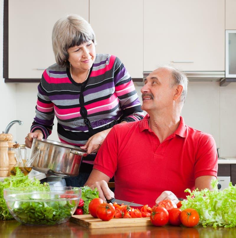 Couples mûrs affectueux faisant cuire dans la cuisine photos stock
