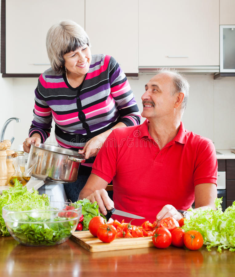 Couples mûrs affectueux faisant cuire dans la cuisine image stock