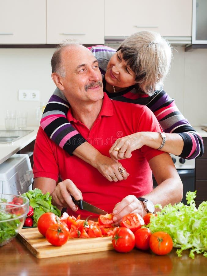Couples mûrs affectueux faisant cuire ensemble images libres de droits