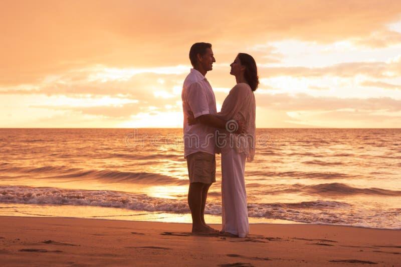 Couples mûrs appréciant le coucher du soleil sur la plage images stock