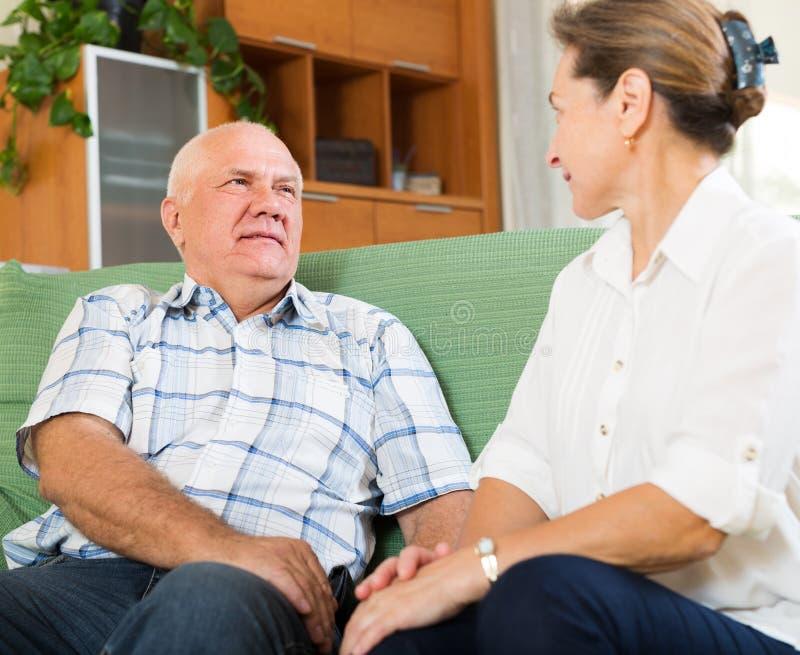 Couples mûrs ayant parler sérieux à la maison photos stock