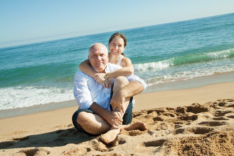 Couples mûrs contre la mer images libres de droits