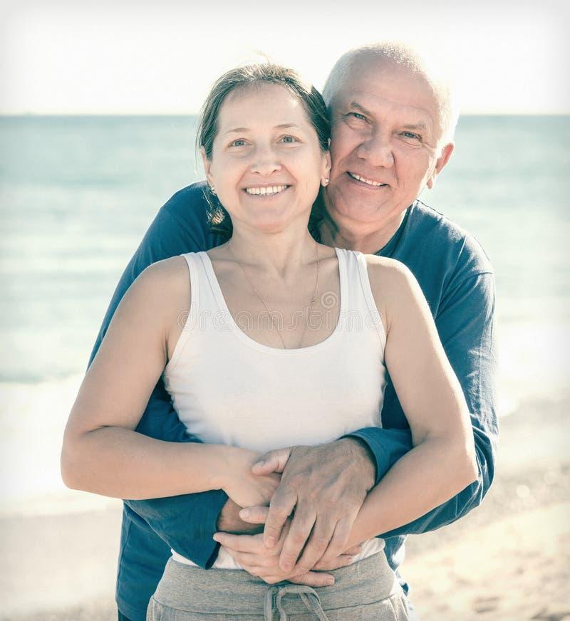 Couples mûrs contre la mer en été photo stock