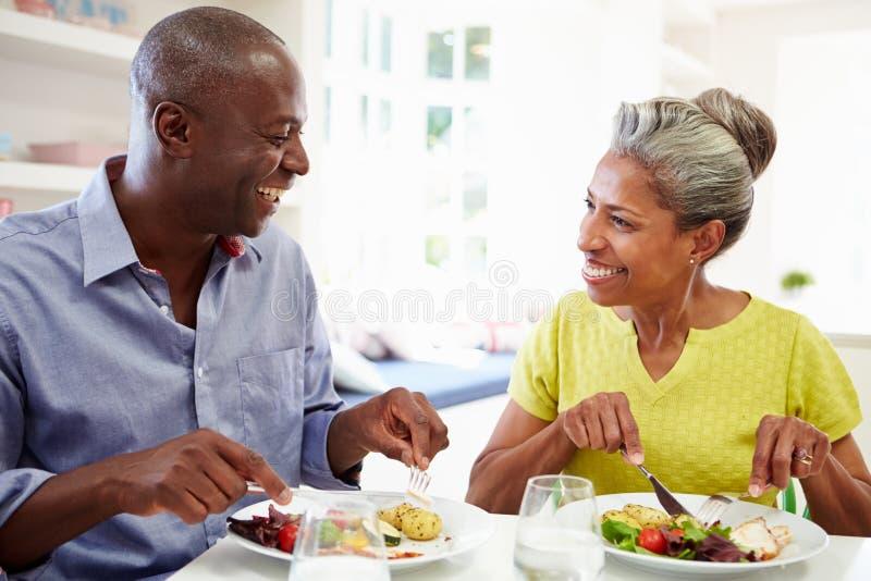 Couples mûrs d'Afro-américain mangeant le repas à la maison images libres de droits