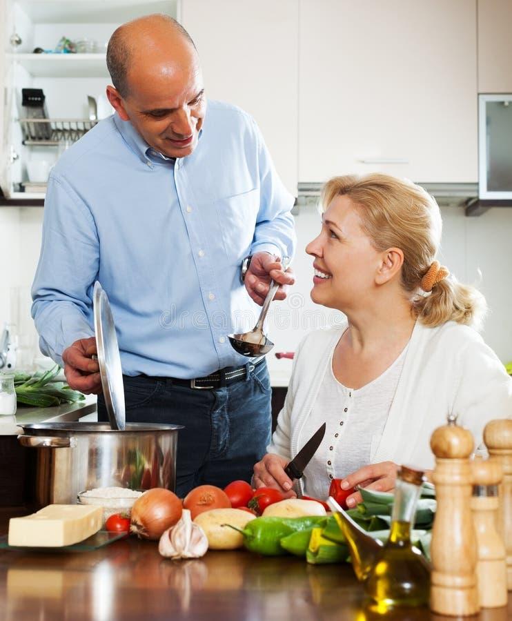 Couples mûrs d'Ordatary faisant cuire la soupe végétarienne photo libre de droits