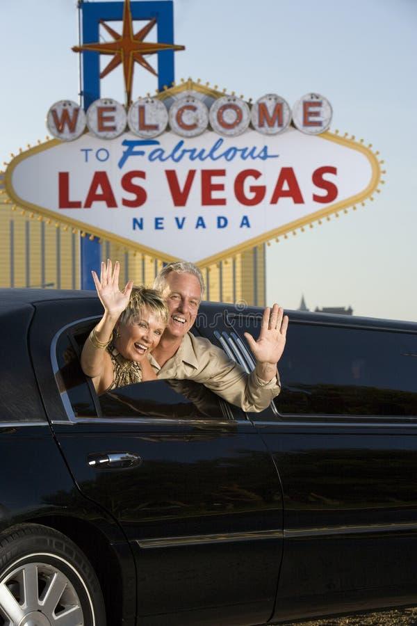 Couples mûrs dans des mains de ondulation de limousine photographie stock