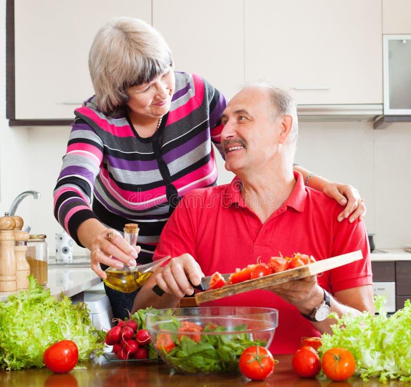 Couples mûrs de sourire faisant cuire ensemble photo libre de droits