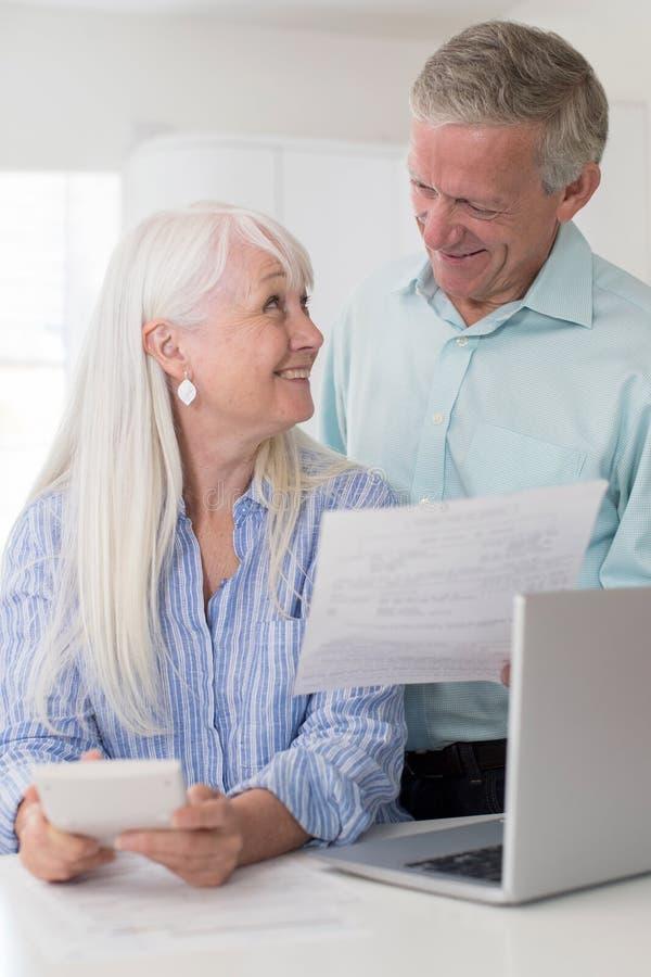 Couples mûrs de sourire passant en revue des finances domestiques photo libre de droits