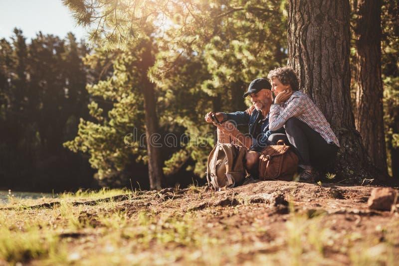 Couples mûrs de sourire recherchant des directions avec la boussole photo stock