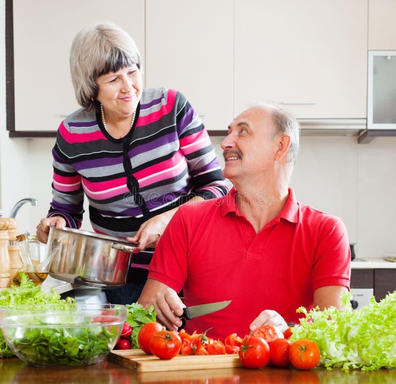Couples mûrs faisant cuire dans la cuisine à la maison photos libres de droits