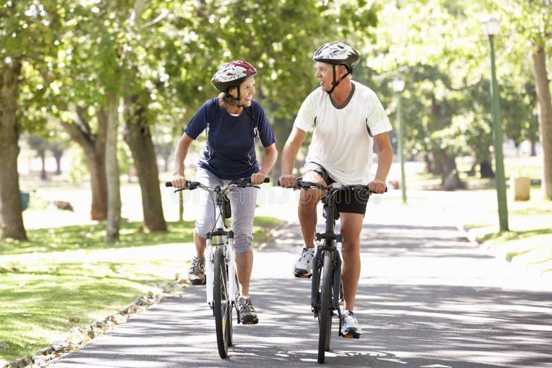 Couples mûrs faisant un cycle par le parc image stock