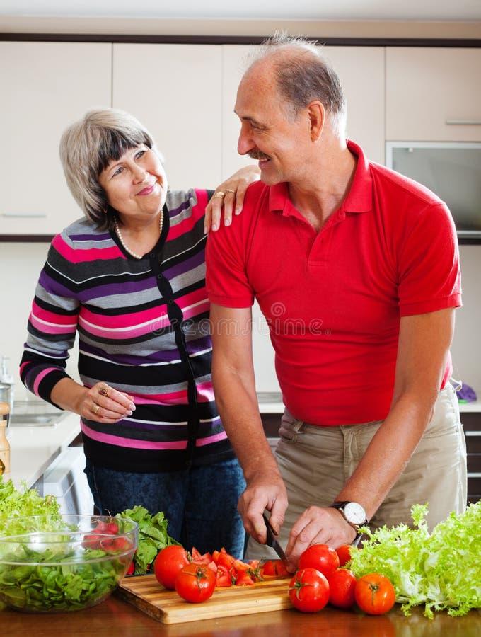 Couples mûrs heureux dans la cuisine à la maison images stock