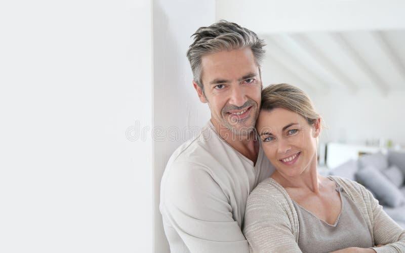 Couples mûrs heureux dans leur maison toute neuve images libres de droits
