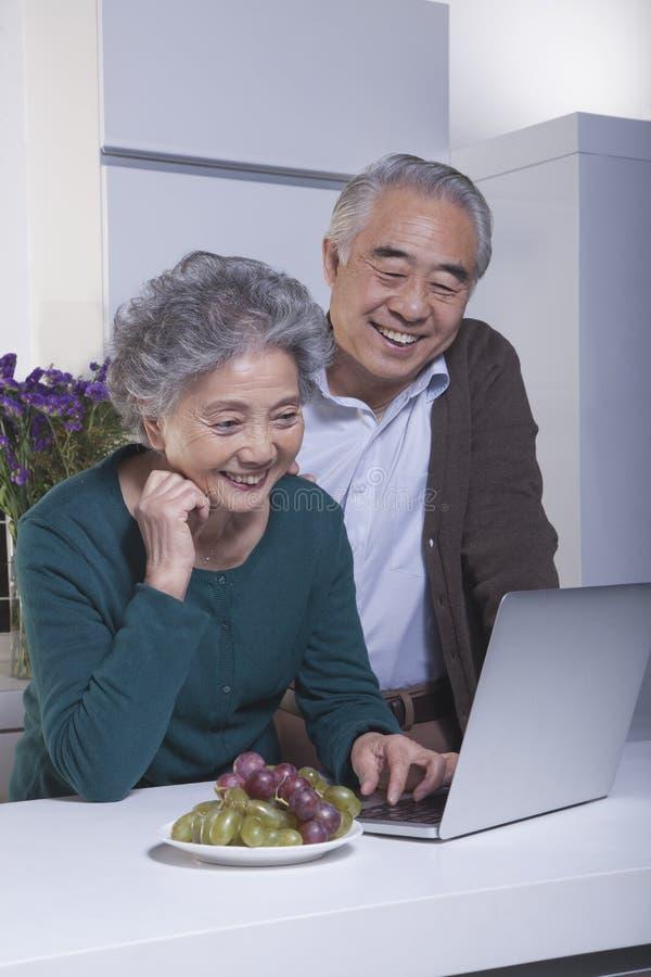 Couples mûrs heureux de sourire regardant l'ordinateur portable dans la cuisine photographie stock