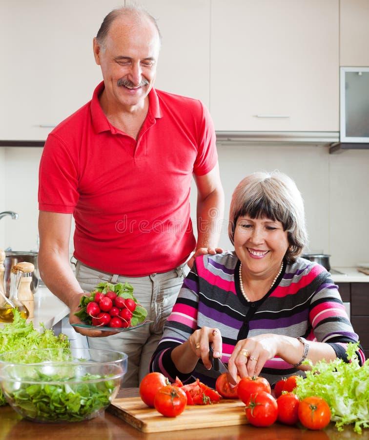 Couples mûrs heureux faisant cuire dans la cuisine photo libre de droits