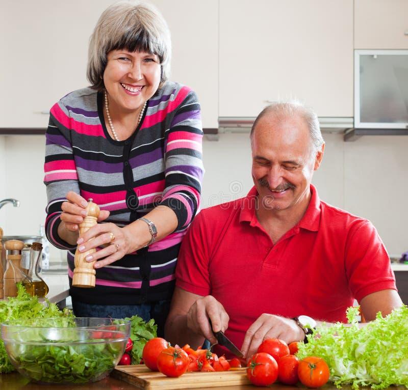 Couples mûrs heureux faisant cuire le déjeuner veggy image stock