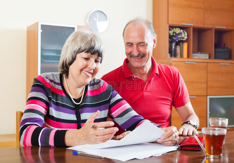 Couples mûrs heureux lisant les documents financiers images libres de droits
