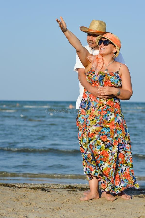 Couples mûrs heureux se tenant à la plage sablonneuse de bord de la mer et tenant des mains images libres de droits