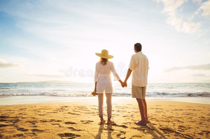 Couples mûrs marchant sur la plage au coucher du soleil photographie stock