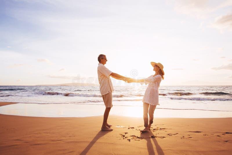 Couples mûrs marchant sur la plage au coucher du soleil photos stock