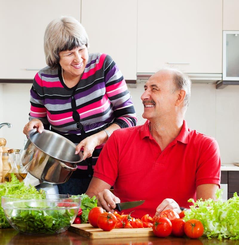 Couples mûrs mariés heureux faisant cuire dans la cuisine photo libre de droits