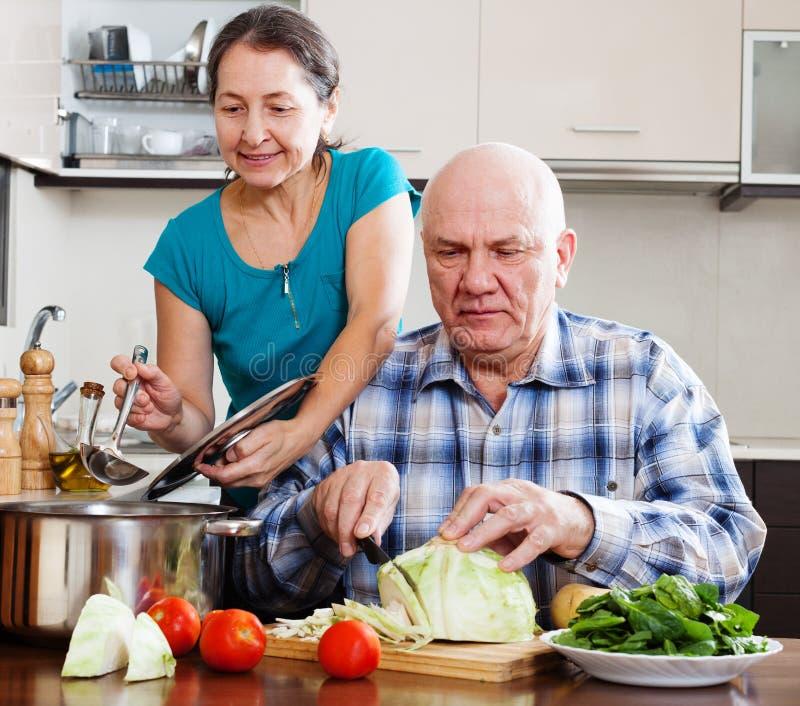 Couples mûrs ordinaires faisant cuire avec des légumes photo stock