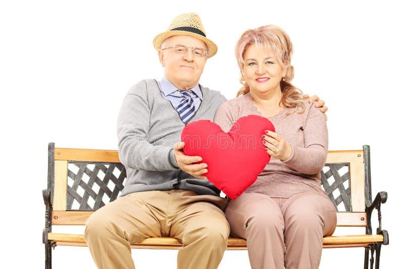 Couples mûrs posés sur le banc tenant un grand coeur rouge photographie stock libre de droits