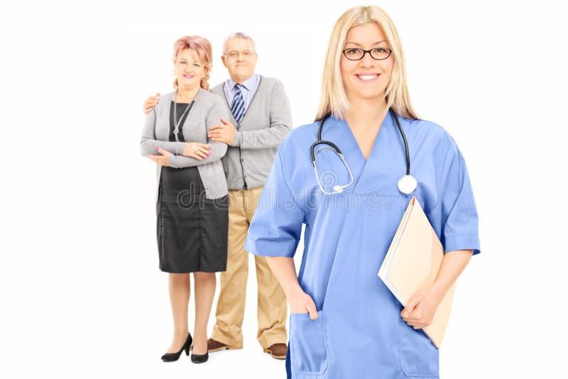 Couples mûrs posant derrière le docteur féminin image stock