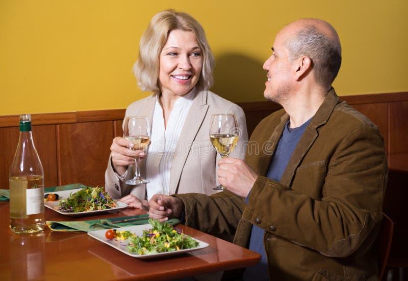 Couples mûrs positifs dînant au restaurant photo stock