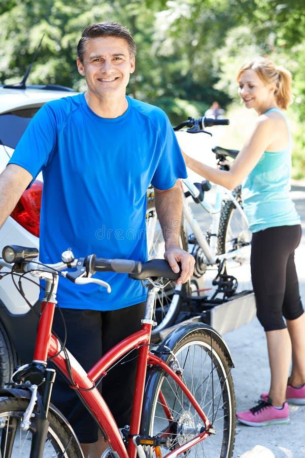 Couples mûrs prenant des vélos de montagne de support sur la voiture image libre de droits