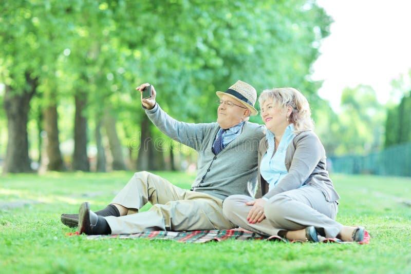 Couples mûrs prenant le selfie sur un pique-nique en parc photos stock