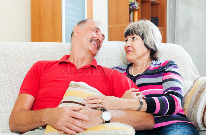 Couples mûrs riants détendant sur le divan photo stock