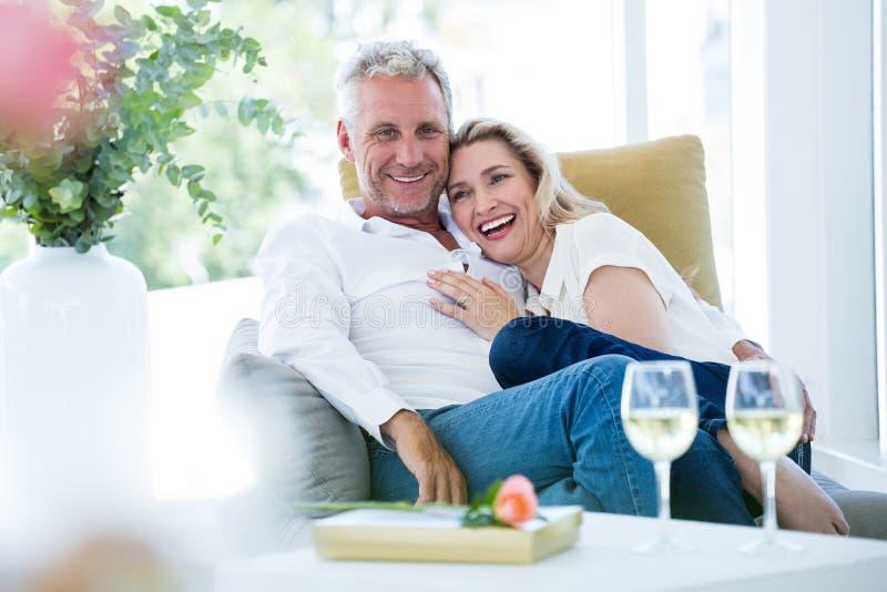 Couples mûrs romantiques heureux se reposant sur le fauteuil photo stock