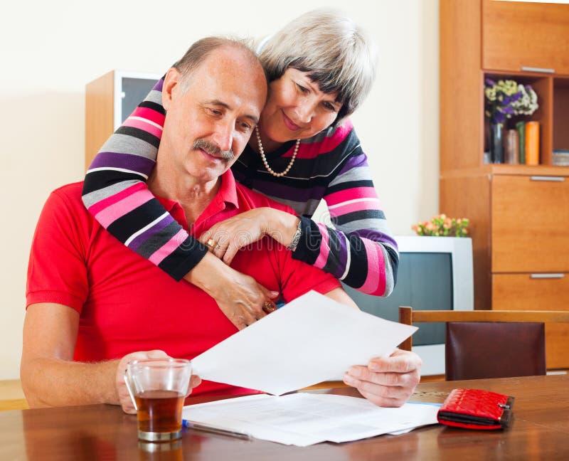 Couples mûrs sérieux regardant le document images stock