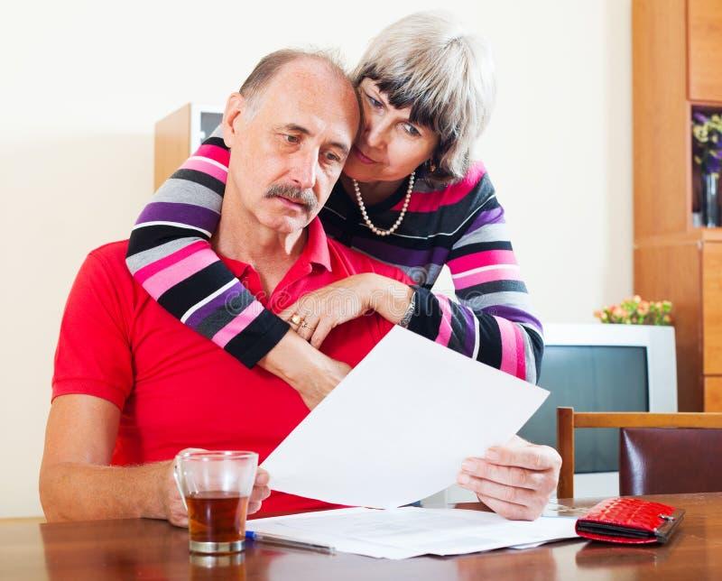 Couples mûrs sérieux semblant le document financier photos libres de droits