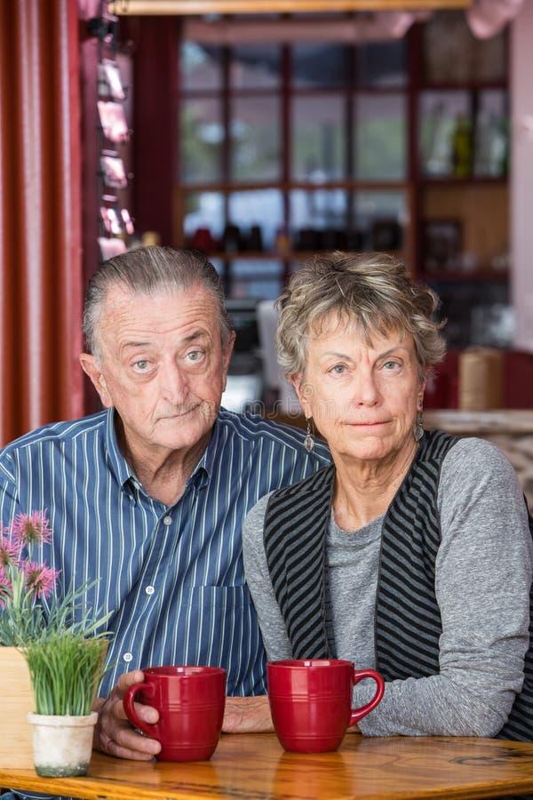 Couples mûrs sceptiques dans le café image libre de droits