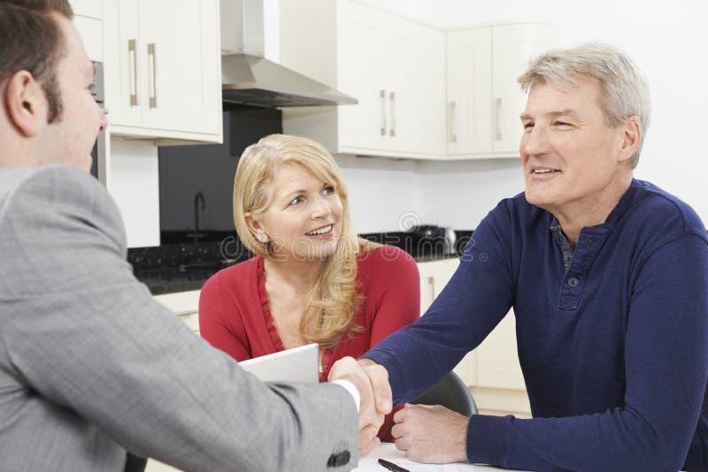 Couples mûrs serrant la main au conseiller financier à la maison photo stock