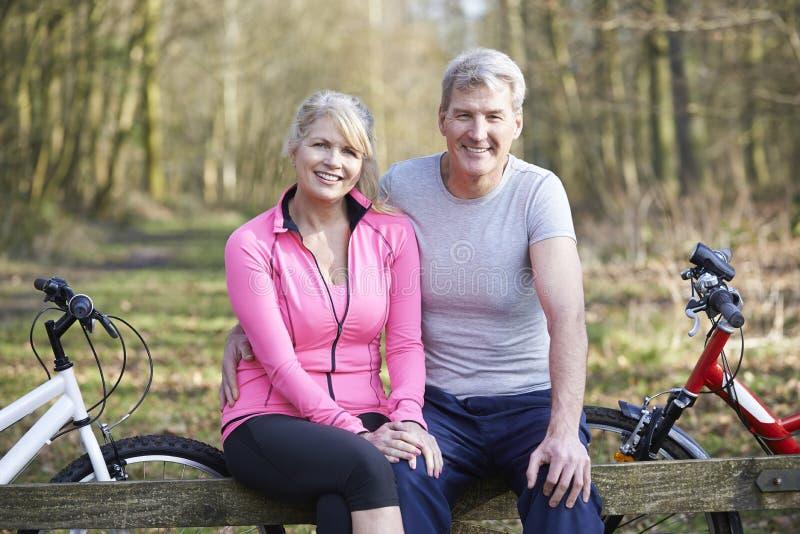 Couples mûrs sur le tour de cycle dans la campagne ensemble photos stock