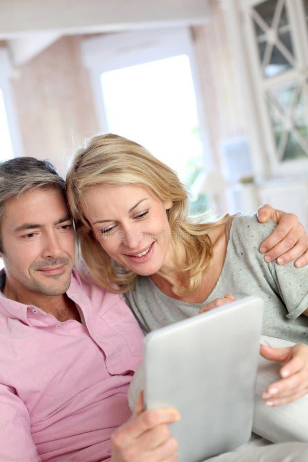 Couples mûrs websurfing sur le comprimé image libre de droits