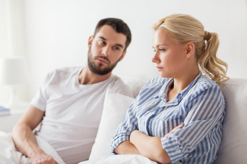 Couples malheureux ayant le conflit dans le lit à la maison photos stock