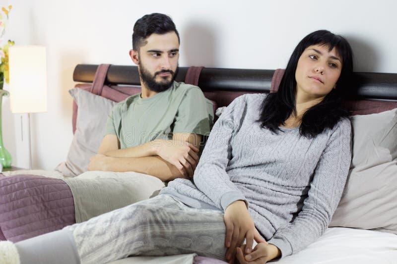 Couples malheureux dans le combat de lit triste images libres de droits