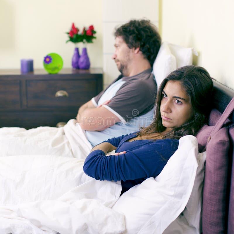 Couples malheureux dans le lit après le combat ne parlant pas le rétro style photographie stock