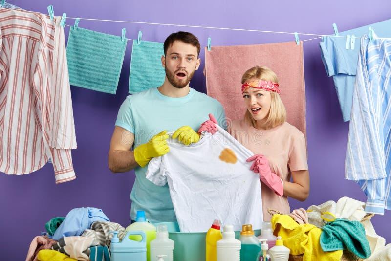 Couples malheureux frustrants tenant le T-shirt blanc avec une tache là-dessus images libres de droits