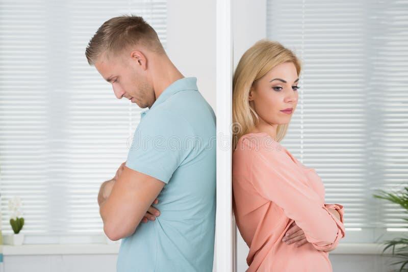 Couples malheureux se tenant de nouveau au dos à la maison photo libre de droits