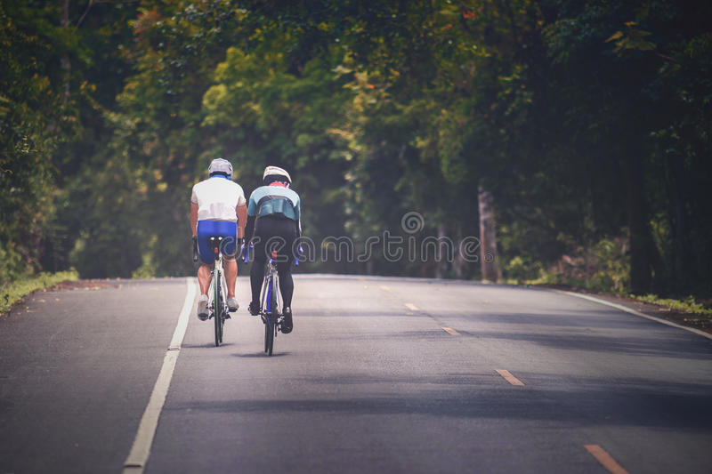 Couples of man riding touring bicycle on mountain road royalty free stock photos