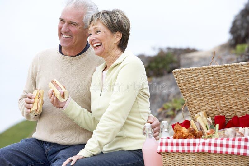 Couples mangeant un repas de fresque d'Al à la plage photos libres de droits