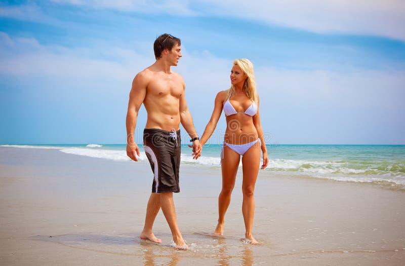 Couples marchant à la plage photo stock