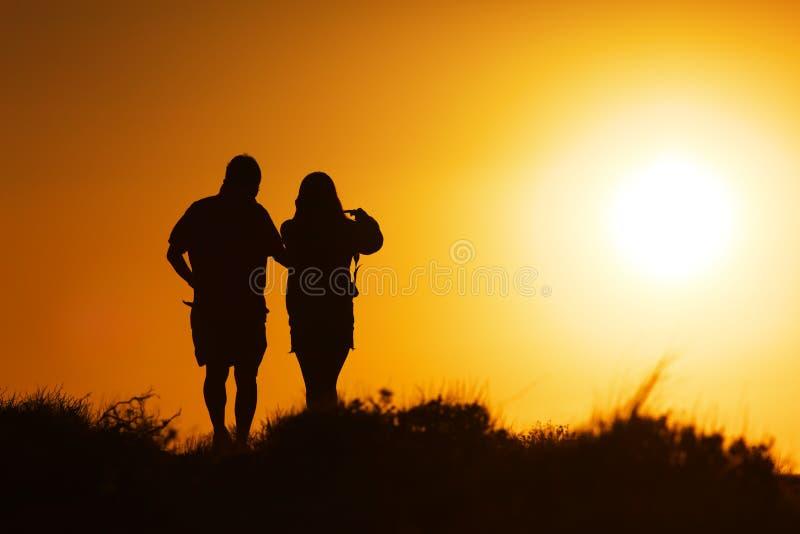 Couples marchant au coucher du soleil images libres de droits