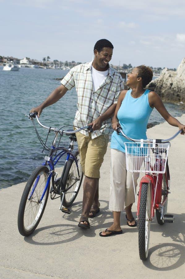 Couples marchant avec des bicyclettes et regardant l'un l'autre sur la plage images stock